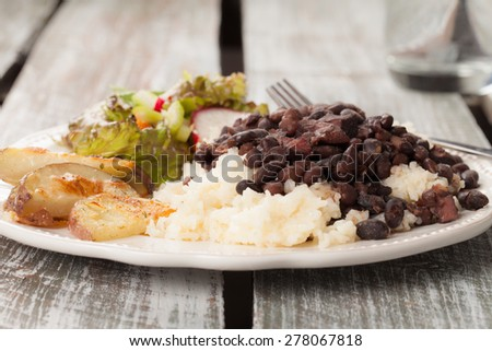 macro shot of traditional Brazilian feijoada with white rice, homemade potato wedges, and green salad with a clear glass of water on an old barn wood table - stock photo