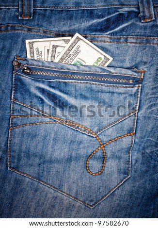 Macro shot of trendy jeans with american 100 dollars bills on its pocket - stock photo