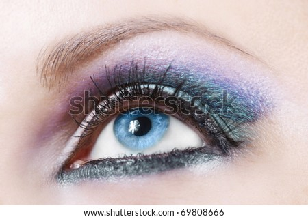 Macro shot of woman eye with violet and blue bright make-up - stock photo