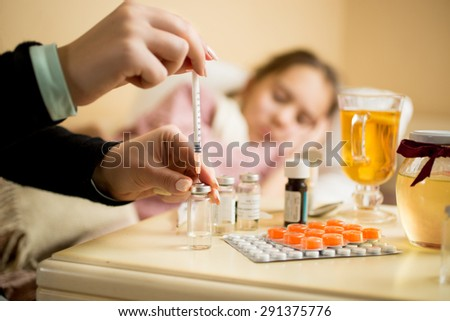 Macro shot of woman filling syringe from ampule with medicines next to patient's bed