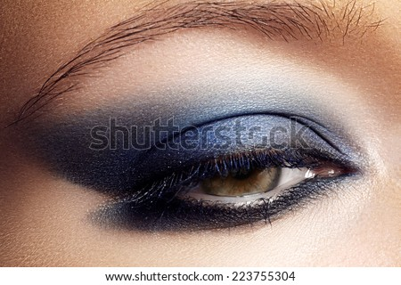Macro shot of woman's beautiful eye, bright and deep colors make-up. Dark blue eyeshadow on eyelid. Sexy view, sensual look. Glamourous chic makeup - stock photo