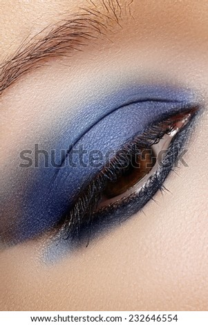 Macro shot of woman's beautiful eye, bright and deep colors make-up. Dark blue eyeshadow on eyelid. Sexy view, sensual look. Glamourous chic makeup