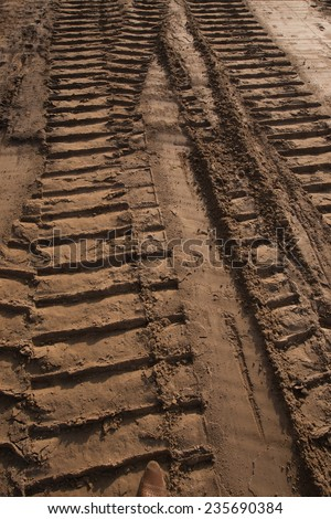 macro texture tire tracks in the sand in sunlight - stock photo
