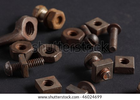 Macro view collection of old rusted nuts and machine screws including a wing nut on a black background