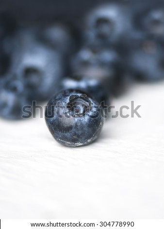 Macro view of a group of blueberries on rustic wooden table, focus on single blueberry, shallow DOF - stock photo