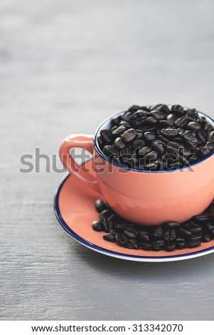 Macro view of a group of dark, roasted coffee beans in a bright orange coffee mug on rustic wooden table, shallow DOF - stock photo