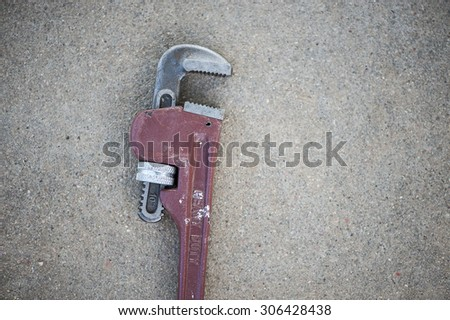 Macro view of a single antique wrench on a concrete surface, shallow DOF - stock photo