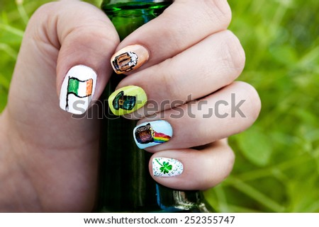 Macro view of a woman's hand holding a beer bottle against green lush background. Her fingernails are adorned with St. Patrick's day themed nail polish art.
