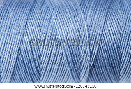 Macro view of blue thread wound on a spool - stock photo