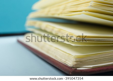 Macro view of book pages on colorful paper background. Copy space for text. - stock photo