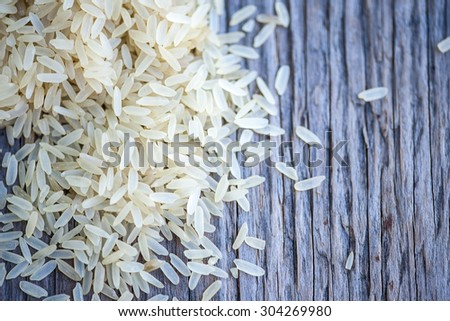Macro view of brown rice on rustic, wooden table, shallow DOF - stock photo