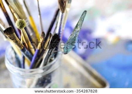 Macro view of dirty paint brushes in glass jar, shallow DOF - stock photo