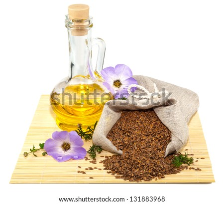 Macro view of flax seeds in flax sack and glass bottle of flax oil isolated on white background - stock photo