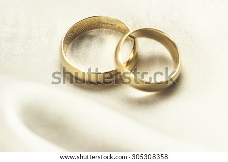 Macro view of gold wedding bands on white silk background, focus on interior engraving: forever yours, shallow DOF