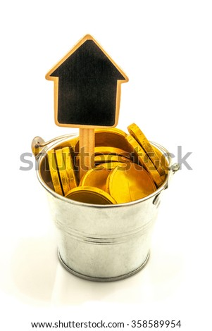 Macro view of metal bucket with gold coins and wooden house isolated on white background - stock photo