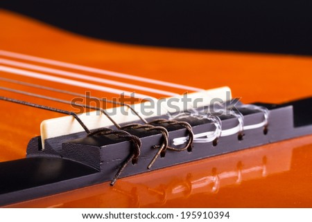 Macro view of orange wooden classical acoustic guitar. - stock photo