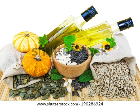 Macro view of raw sunflower seeds and pumpkin seeds in flax sacks and sunflower and pumpkin oil isolated on white background - stock photo