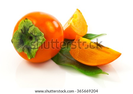 Macro view of ripe fresh persimmon with slices and leaves isolated on white background - stock photo