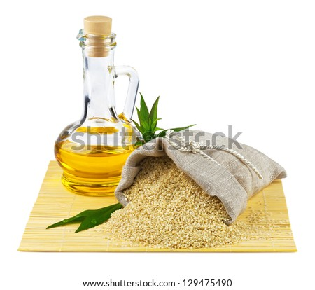 Macro view of sesame seeds in flax sack and glass bottle of sesame oil isolated on white background - stock photo
