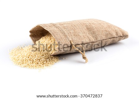 Macro view of sesame seeds in flax sack with tie isolated on white background