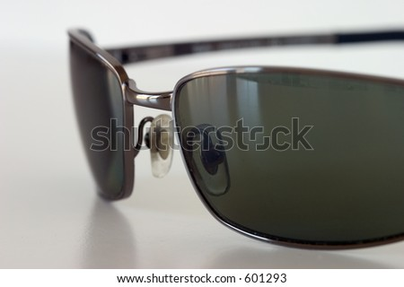 Macro view of sunglasses sitting on a white surface. - stock photo