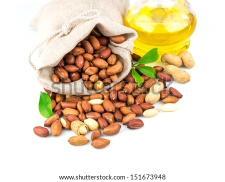 Macro view of tasty peanut in flax sack and glass bottle of oil with leaves isolated on white background - stock photo