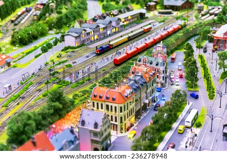 Macro view of toy hobby railroad layout with railway station building, passenger and freight cargo trains on rail tracks - stock photo