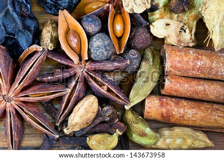 macro view of various spices for mulled wine on wooden table - stock photo