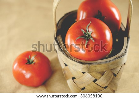 Macro view of vibrant, red tomatoes in brown wicker basket, shallow DOF - stock photo