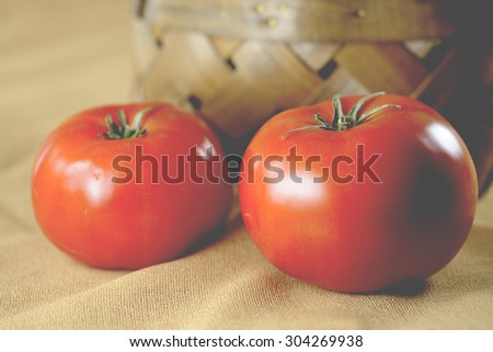 Macro view of vibrant, red tomatoes with brown wicker basket in the background, shallow DOF - stock photo