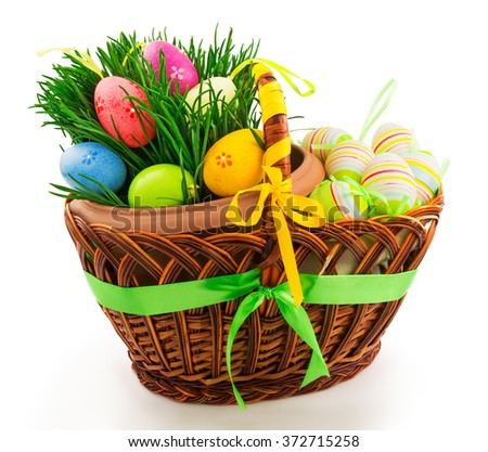 Macro view of wicker wooden basket with Easter eggs, fresh grass and color ribbons isolated on white background