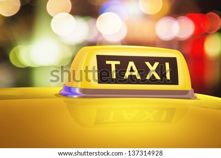 Macro view of yellow taxi sign on car in evening or night city street outdoors - stock photo