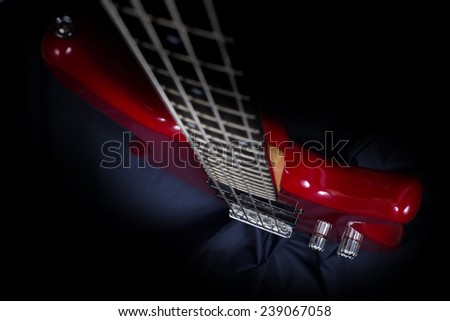 Macro view on glassed classic bass  red electric guitar with four strings and three control knobs on deep blue dark fabric background - stock photo