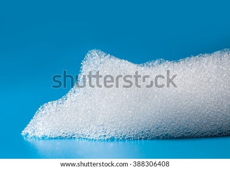 Macro view white soapy bubbles foam. suds and shower texture. Blue background. Horizontal, soft focus - stock photo