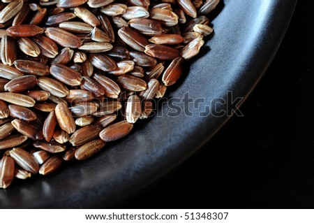 Macro views of red rice grains in a black bowl