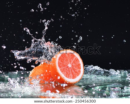 Macro water splash on grapefruit. Water drops with juicy grapefruit - stock photo