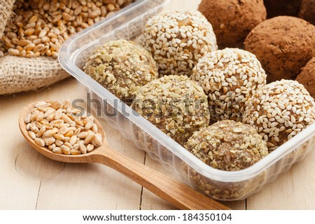 macrobiotic healthy food: balls from ground wheat sprouts with sesame, pumpkin seeds and chocolate sprinkles in plastic box; sprouted grains in wooden spoon - stock photo