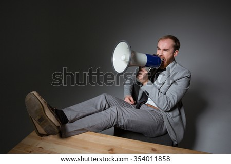 Mad annoyed businessman in grey suit sitting and shouting in megaphone over grey background - stock photo