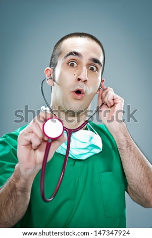 Mad Doctor with a Stethoscope Over a Grey Background - stock photo