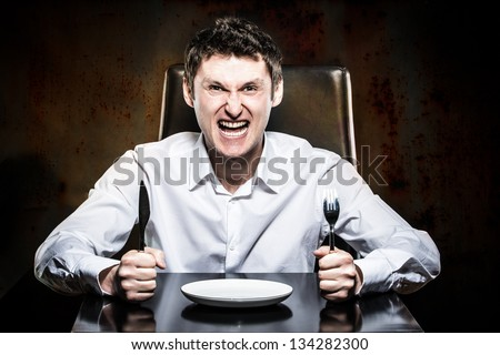 Mad man waiting his food in a restaurant - stock photo