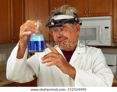 Mad scientist brews up a concoction at home in the kitchen - stock photo