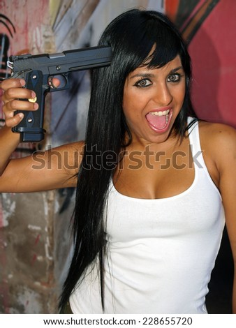 Mad woman with a gun pointing to her head - stock photo