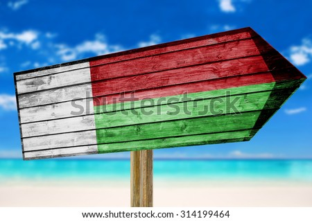 Madagascar Flag wooden sign on beach background - stock photo