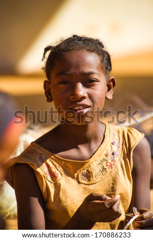 MADAGASCAR - JULY 1, 2011: Portrait of an unidentified girl wearing a yellow dress in Madagascar, July 1, 2011. People of Madagascar suffer of poverty due to the unstable situation.