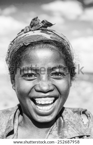 MADAGASCAR - JUNE 30, 2011: Portrait of an unidentified smiling woman working in the field in Madagascar, June 30, 2011. People of Madagascar suffer of poverty due to the unstable situation. - stock photo