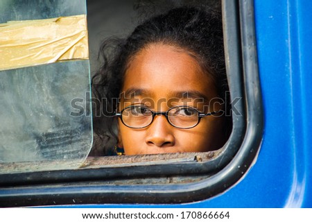 MADAGASCAR - JUNE 28, 2011: Unidentified Madagascar girl smiles for the camera through the bus window in Madagascar, June 28, 2011. Children of Madagascar suffer of poverty due to unstable situation.