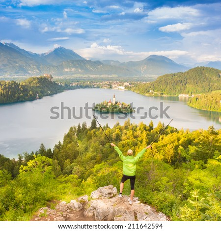 Made it. Young spoty active lady with hiking sticks and hands rised admiring beautiful nature around Bled Lake in Julian Alps, Slovenia.  - stock photo