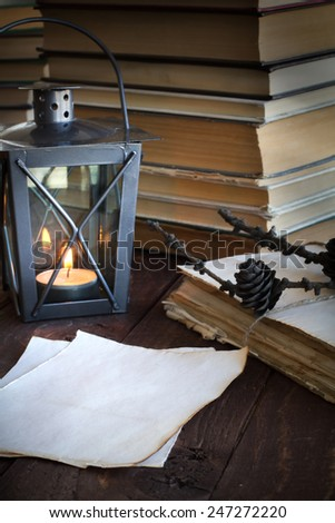 made old sheets of paper, books and candle on a wooden table