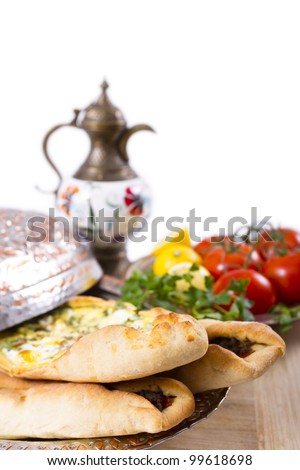 Made with cheese and seasoned ground beef Turkish pide garnished with lemon parsley and tomatoes on the vine. Served with ayran ibrik, and copper plate. - stock photo