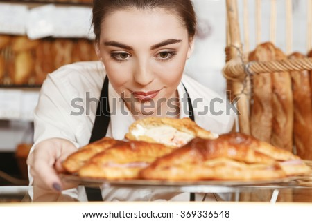 Made with love. Beautiful young female baker placing freshly baked croissants to the showcase - stock photo